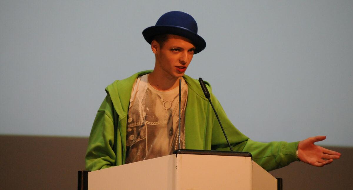 M steht an einem Redner*innenpult. Es trägt einen blauen Hut.