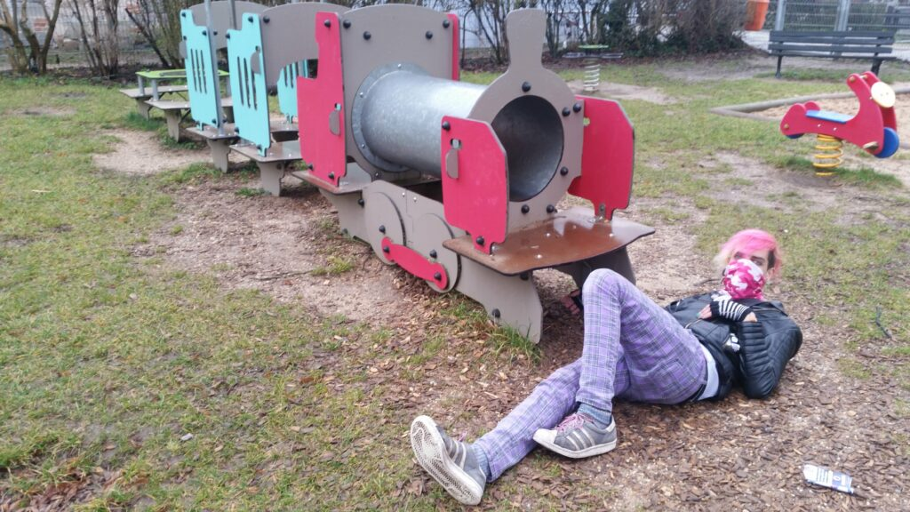 Phant liegt auf einem Spielplatz vor einem Zug